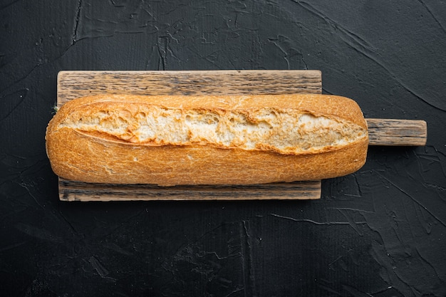 Freshly baked baguette bread, on black background, top view flat lay