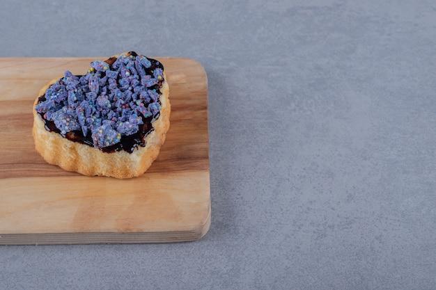 Fetta di torta di mirtilli appena sfornata sul bordo di legno