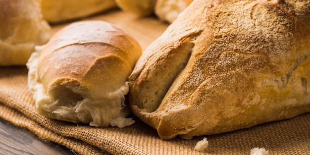 Freshly baked bread loaves on burlap dark wooden. texture closeup italian bakery products