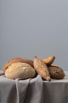 テーブルクロスで覆われたテーブルの上で焼きたてのパンにはコピースペースが含まれています