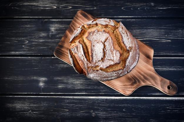 暗いキッチンテーブル、上面図で焼きたてのパン