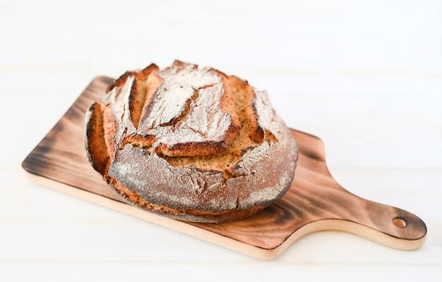 白い背景で隔離の木製まな板に焼きたてのパン