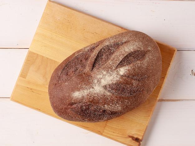 Свежеиспеченный хлеб на деревянном столе на белом деревянном кухонном столе
