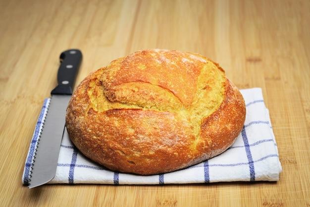 나무 식탁 위에 갓 구운 빵 나무 테이블에 칼을 꽂은 흰 빵 덩어리