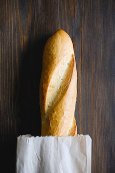 Freshly baked bread in a paper bag on a wooden table
