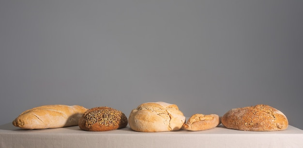 Freshly baked bread on a table covered with a tablecloth with copy space, horizontal
