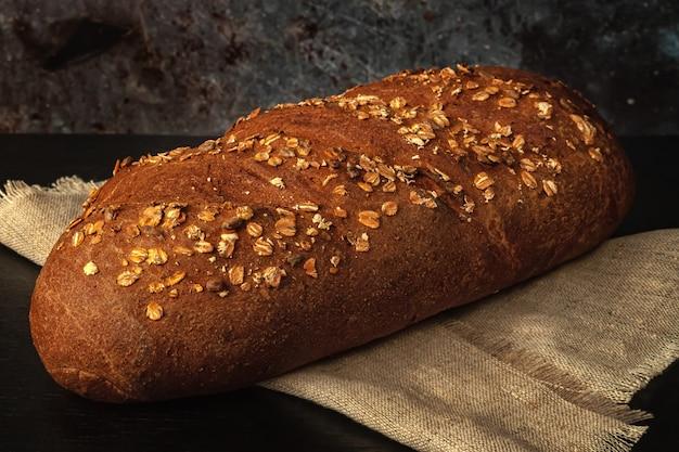 テーブルの上にふすま、ヒマワリの種、オートミールと焼きたてのパン