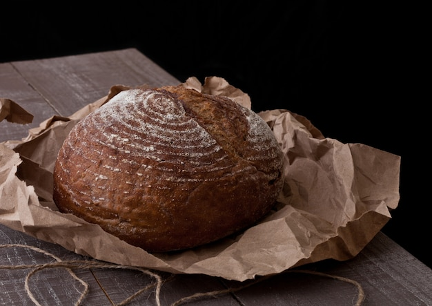Freshly baked  bread with on brown oven paper on wooden board