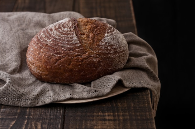 Freshly baked  bread with kitchen towel on dark wooden board