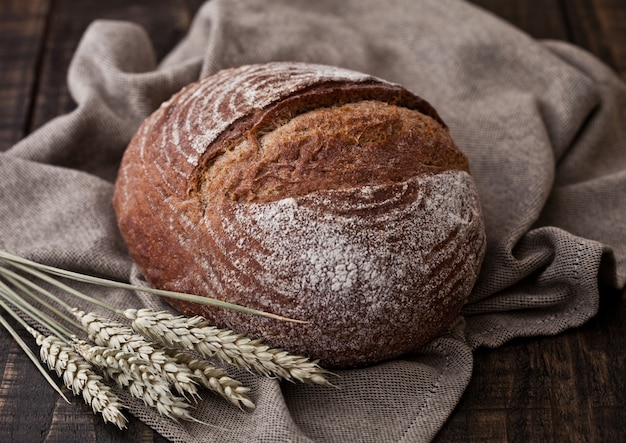 Freshly baked  bread with kitchen towel and wheat on dark wooden board