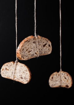 Freshly baked bread with oats hanging on rope on black background