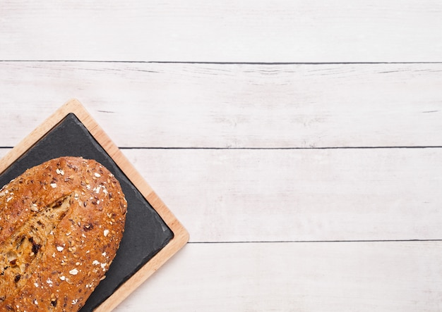 Freshly baked  bread with oats and kitchen towel on wooden board background