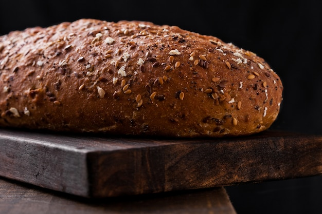 Freshly baked  bread with oats on wooden board background
