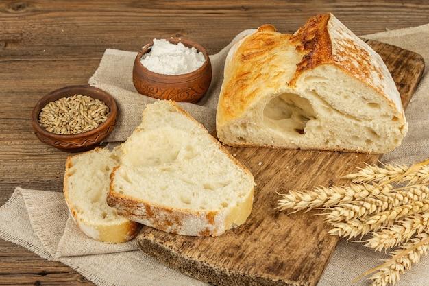 まな板の上に小麦の穂、香りのよい部分が付いている焼きたてのパン。ヴィンテージの木板テーブル、焼き菓子、コピースペース