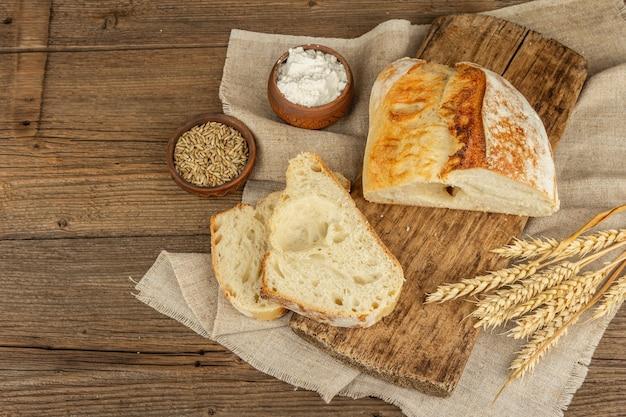 まな板の上に小麦の穂、香りのよい部分が付いている焼きたてのパン。ヴィンテージの木板テーブル、焼き菓子、上面図