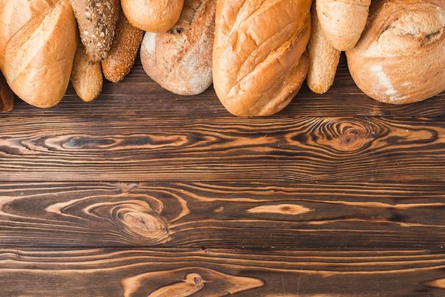 Freshly baked breads at the top of wooden background