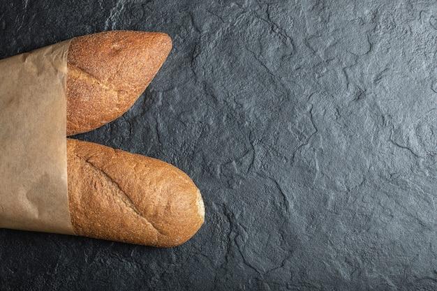 Freshly baked british baton loaf bread on black background.