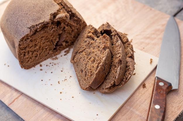 Свежеиспеченная булочка из коричневого бородинского хлеба, нарезанная ломтиками, рядом с большим ножом. свежая домашняя выпечка. выборочный фокус.