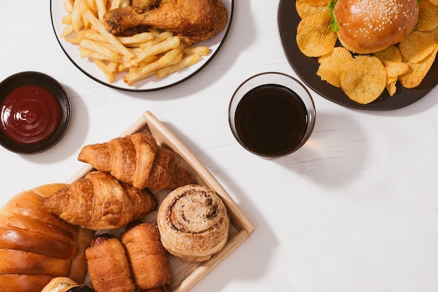갓 구운 빵, 큰 햄버거, 바삭한 치킨 튀김, 흰색 테이블에 감자튀김 - 건강에 해로운 음식 개념