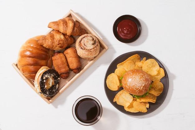 갓 구운 빵, 흰색 테이블에 큰 햄버거 - 건강에 해로운 음식 개념