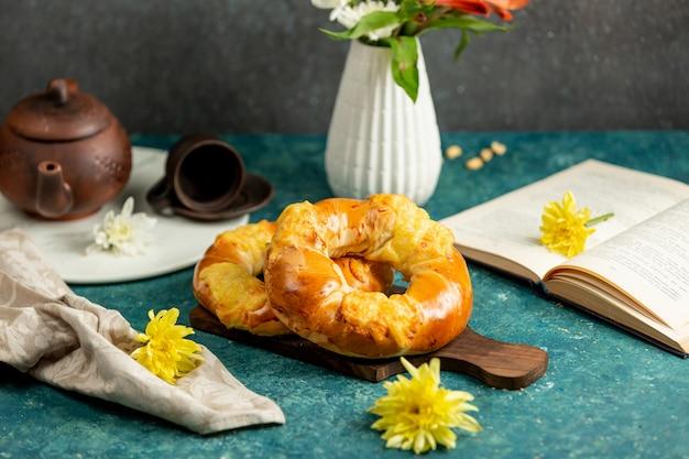 丸い形、黄色の花、開いた本で焼きたてのパン