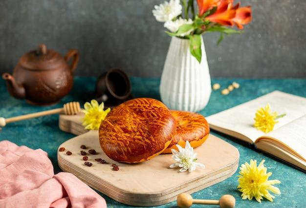 まな板、開いた本、黄色の花の上に横たわる焼きたてのパン
