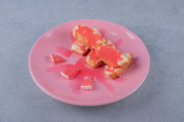 분홍색 접시에 갓 구운 케이크와 자몽 슬라이스