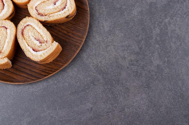Freshly baked cake rolls on wooden plate over grey background.