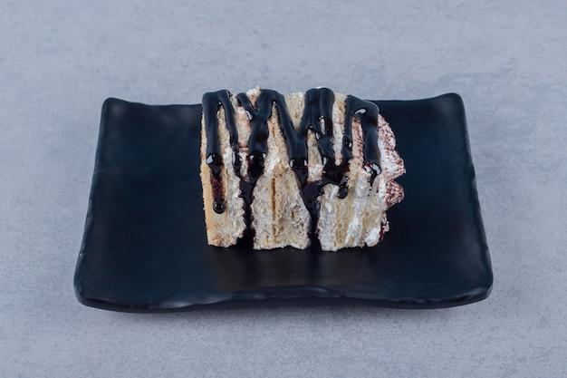 Fetta di torta appena sfornata con salsa al cioccolato sulla banda nera