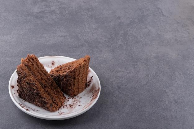 회색 배경 위에 흰색 접시에 갓 구운 된 케이크 조각.