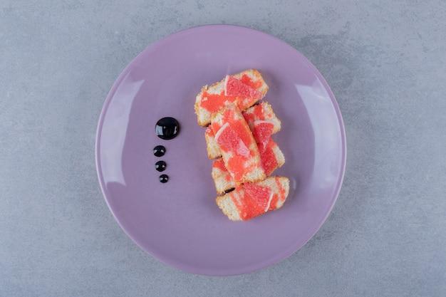 보라색 접시에 자몽과 갓 구운 케이크