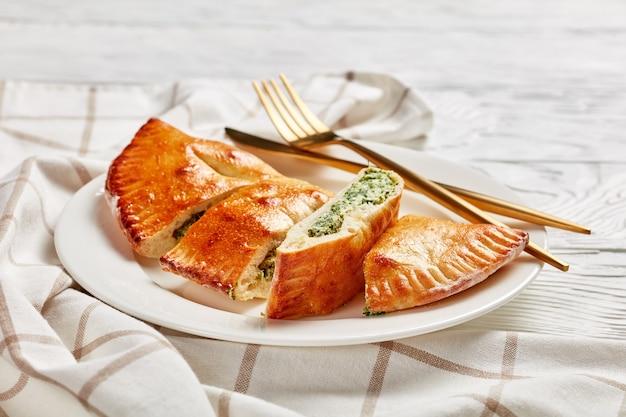 갓 구운 칼 조네, 시금치와 치즈 충전물로 마감 된 피자는 나무 테이블, 이탈리아 요리, 클로즈업에 황금 포크와 나이프가 달린 하얀 접시에 제공됩니다.