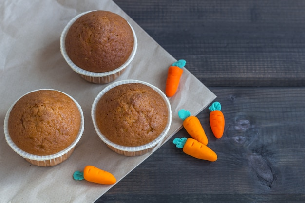 Freshly baked carrot muffins decorated marzipan carrots on wooden background. national carrot cake day.