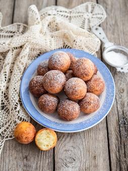 Свежеиспеченные сыр пончики с сахарной пудрой на плите на деревянном столе деревенском. атмосфера уютного домашнего завтрака. закройте, скопируйте пространство.