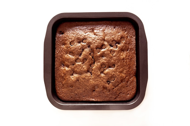 Freshly-baked chocolate chip brownie in a pan isolated