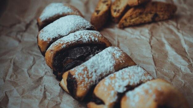 Свежеиспеченные шоколадные рулетики с восхитительной начинкой, посыпанные сахарной пудрой. на фоне крафт-бумаги коричневого цвета