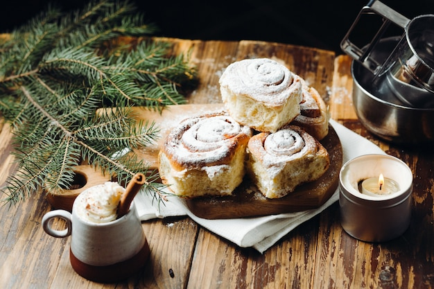 Freshly baked christmas buns with powder and a hot cocoa with cinnamon stick over rustic festive table.