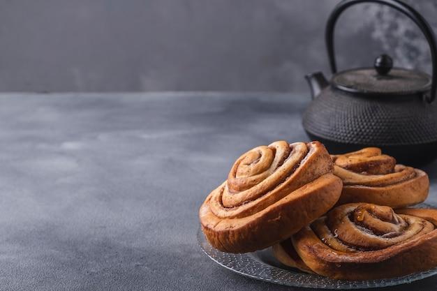 Свежеиспеченные булочки с корицей на тарелке с копией пространства
