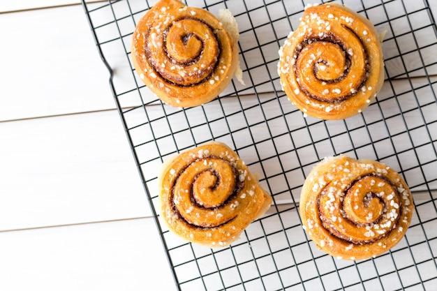 Свежеиспеченные булочки с корицей со специями на деревянном фоне. канельбуле - шведский десерт. концепция питания. вид сверху, плоская планировка