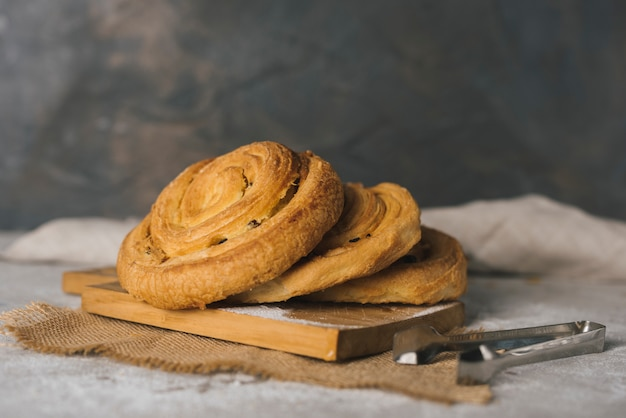 Freshly baked cinnamon rolls buns on chopping board with tong