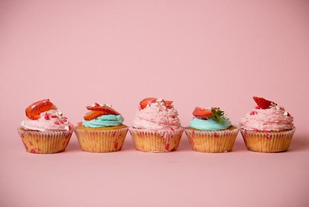 분홍색 배경에 뿌리와 딸기로 장식 된 갓 구운 다채로운 컵 케이크