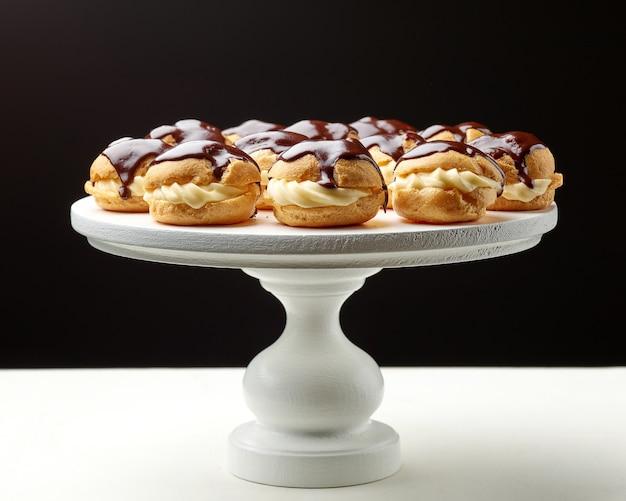 白い木製のケーキスタンドに焼きたてのシュークリーム
