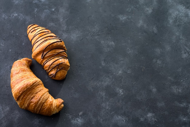 Freshly baked croissant decorated with chocolate sauce isolated