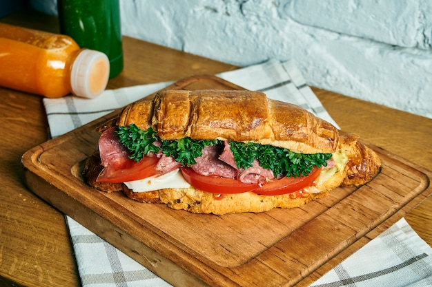 Freshly baked croissant sandwich with cheese, salami, tomatoes and lettuce on a wooden board. food flat lay. tasty breakfast