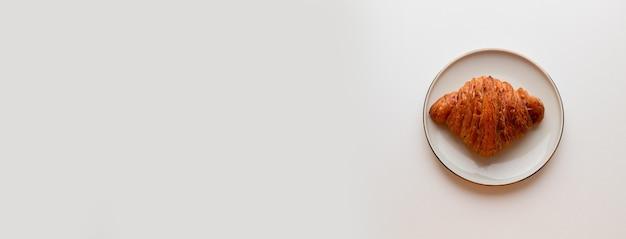 회색 배경에 접시에 카라멜 채우는 갓 구운 크로와상 최소한의 구성 평면 누워 평면도