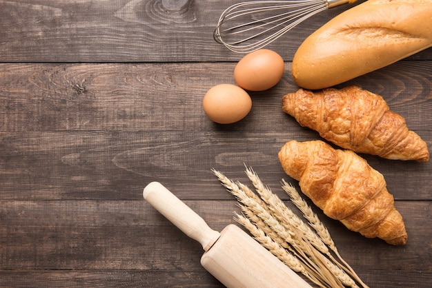 Freshly baked croissants, baguette and eggs on wooden background