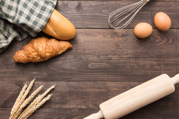 Freshly baked croissants, baguette and eggs on wooden table