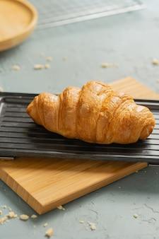 Freshly baked croissants on black plate.