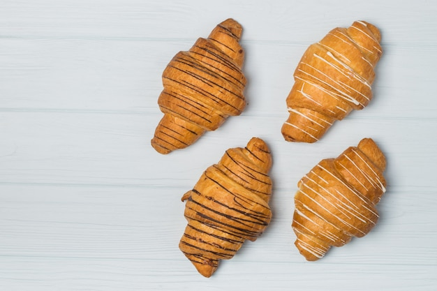 Freshly baked croissants and coffee cup on grey table, top view