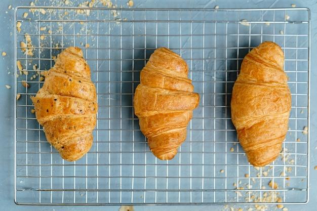Freshly baked croissants on cooling rack.